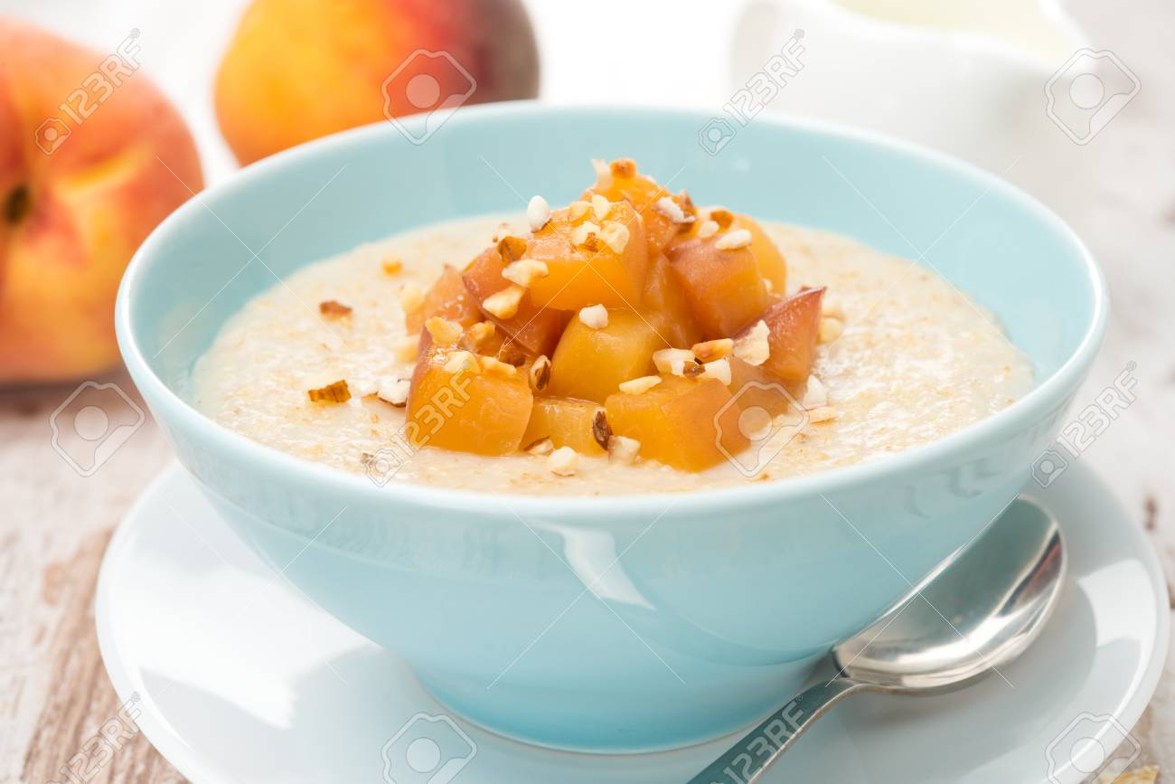 oatmeal with caramelized peaches in a bowl and jug of yogurt for breakfast, close-up, horizontal - 23248563