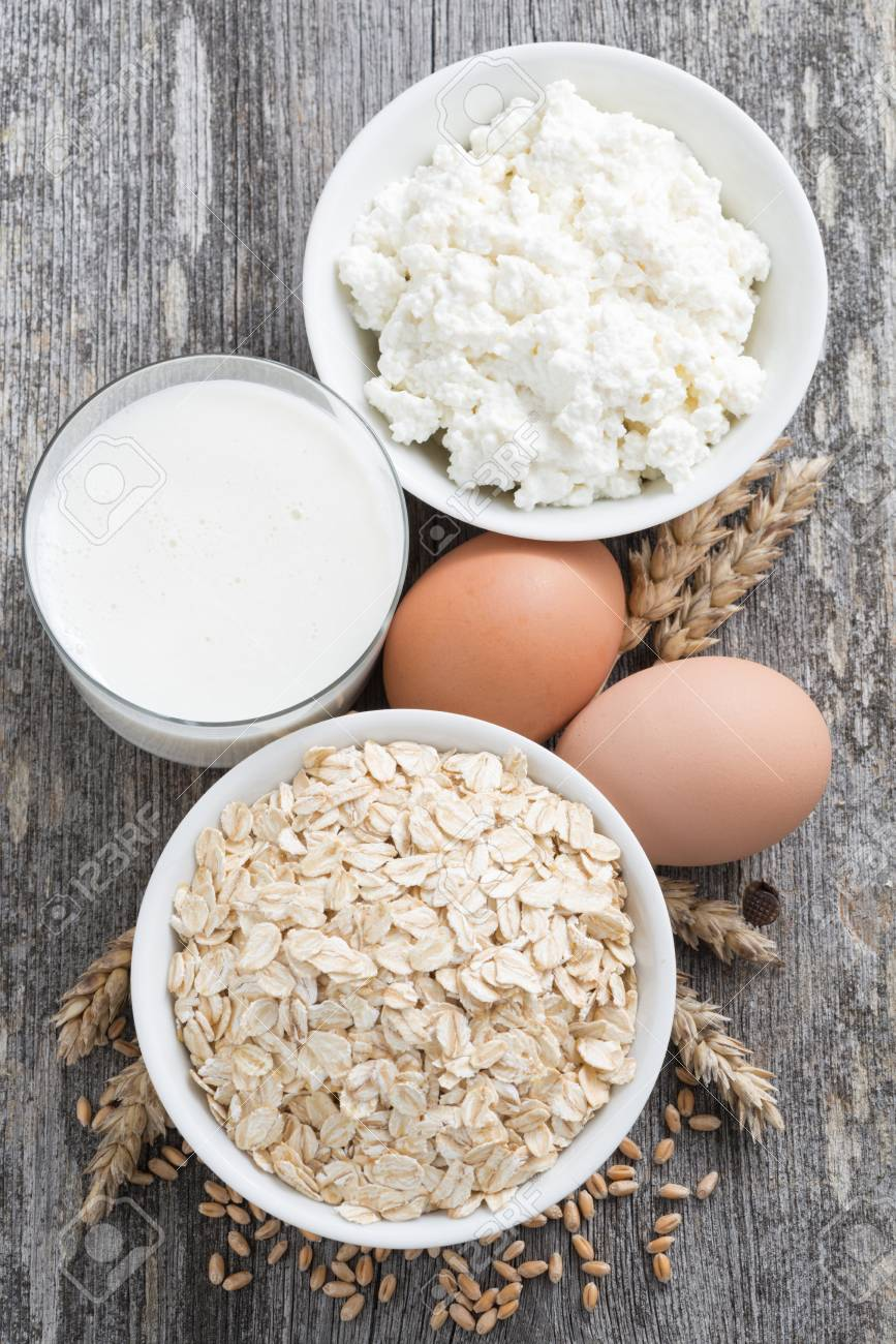 Fresh Products   Oatmeal, Eggs, Cottage Cheese And Milk, Top View, Vertical