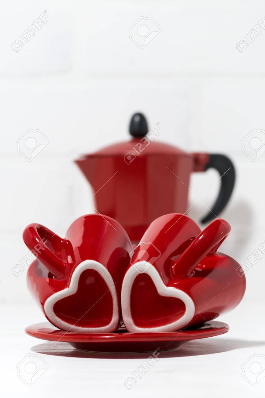 red coffee cups with hearts and a coffee pot vertical closeup stock