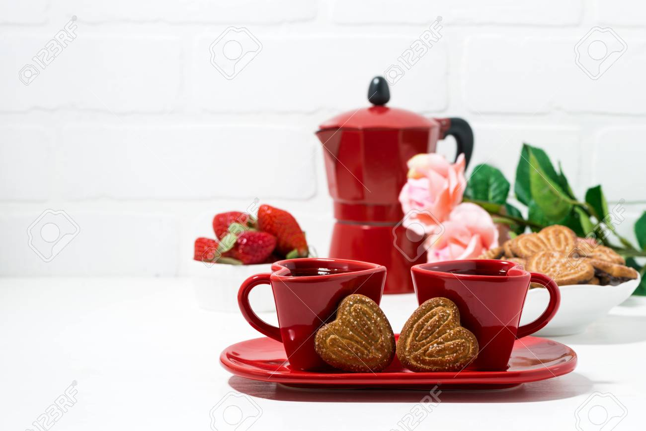 two red coffee cups and heart shaped cookies on white background