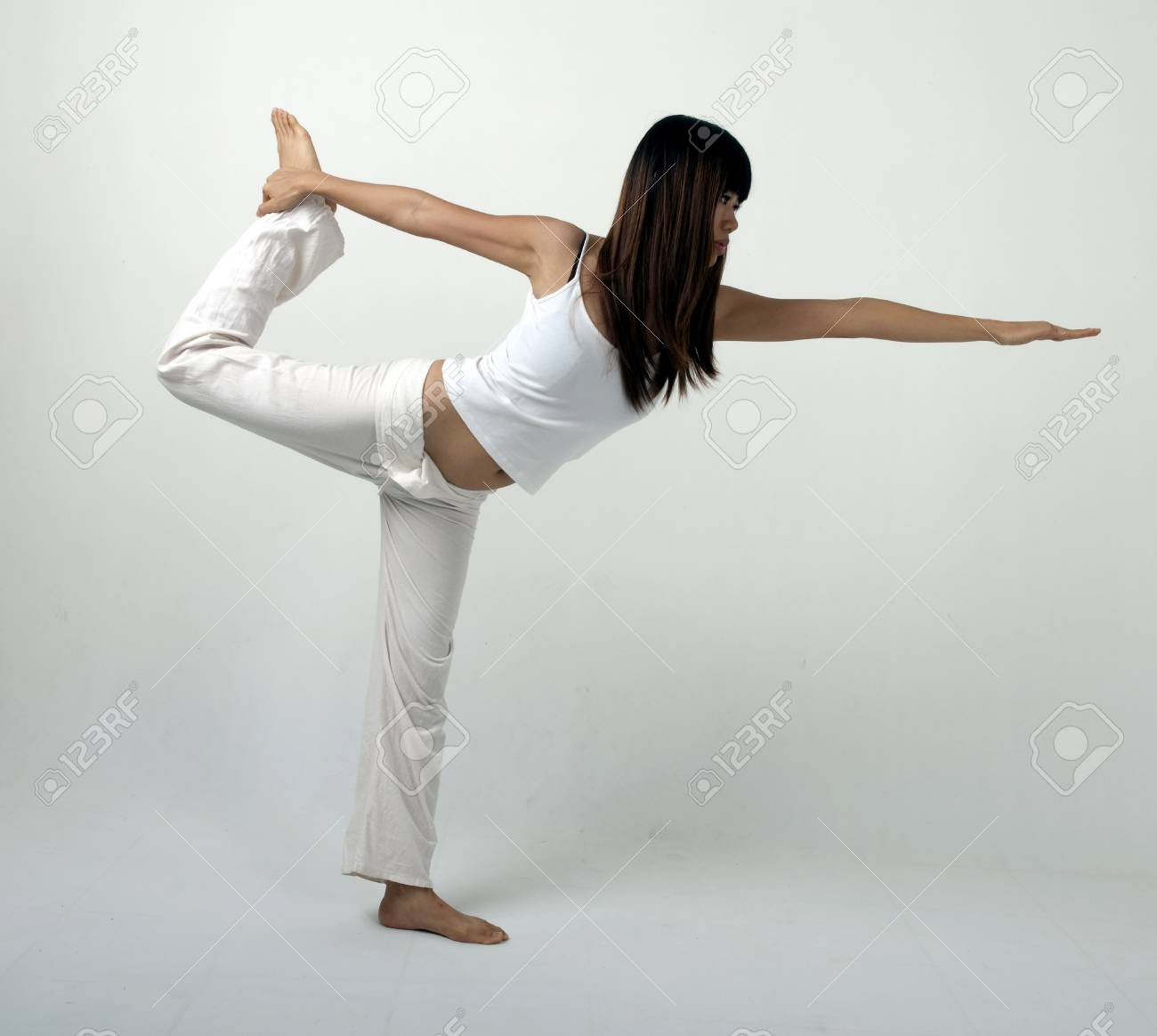 asian girl performing yoga  stand position with light background Stock Photo - 6973814