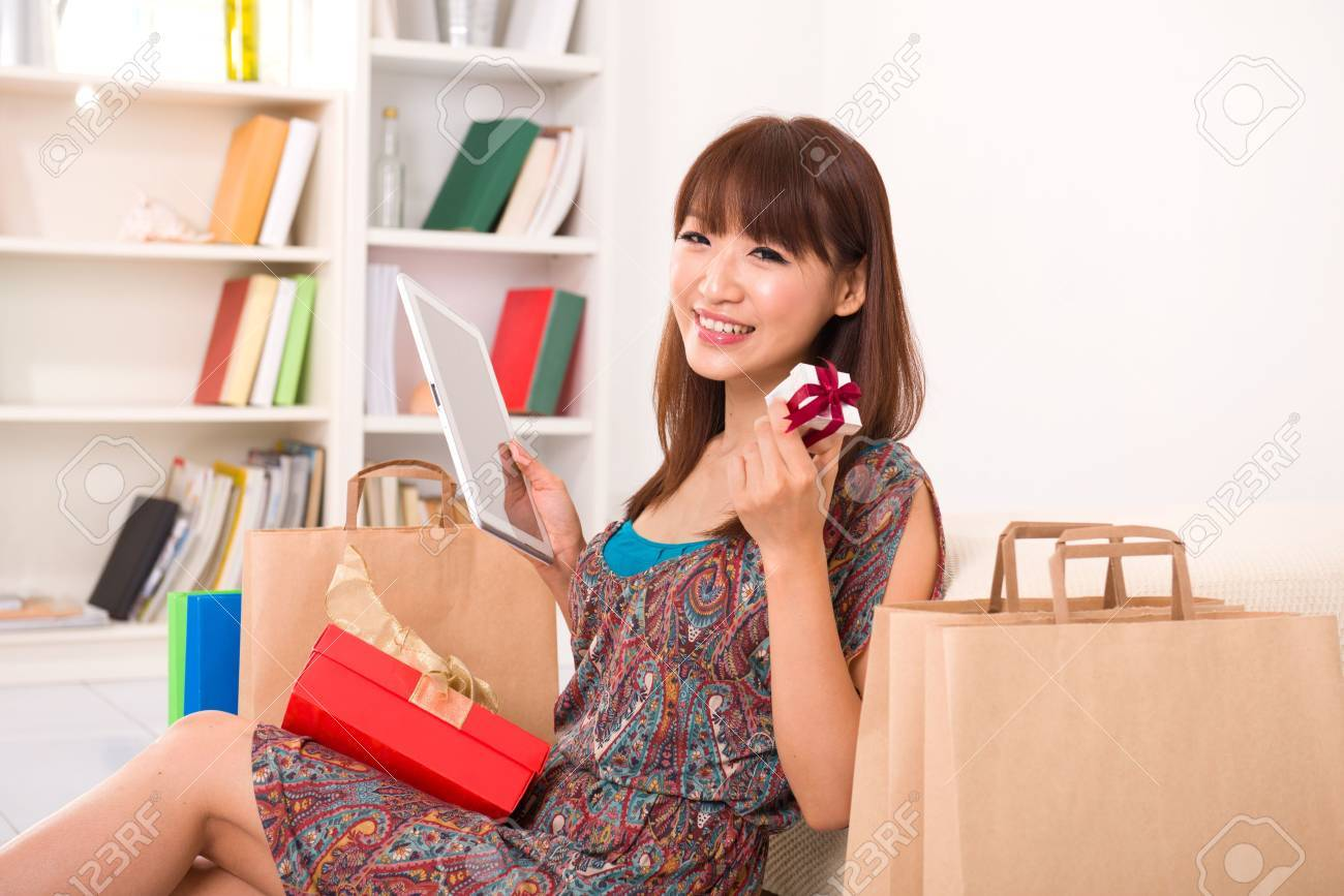 asian girl enjoying online shopping from home, showing off a present Stock Photo - 16323594