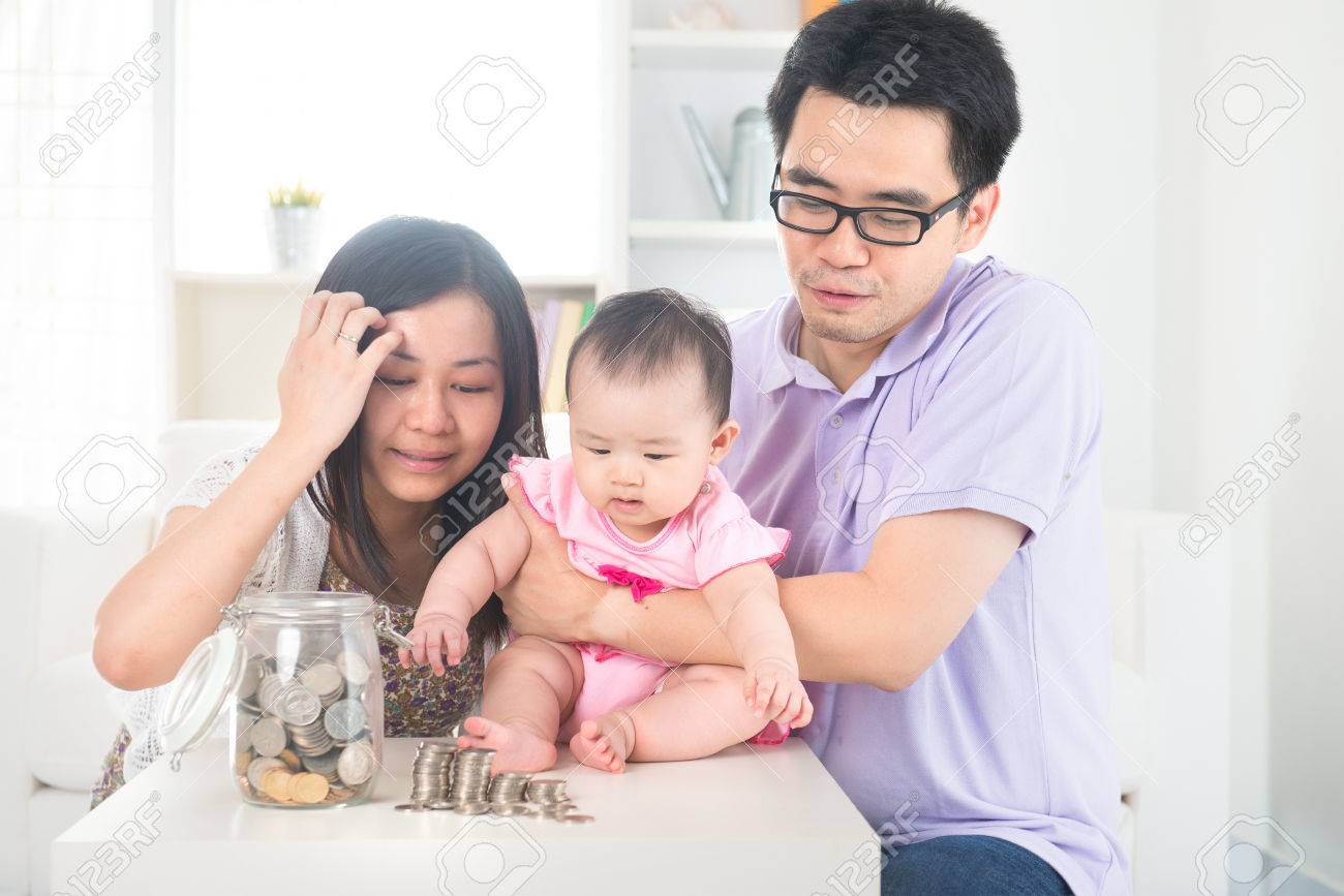 Asian baby putting coins into the glass bottle with help of parents. Money saving education concept. Stock Photo - 22639495