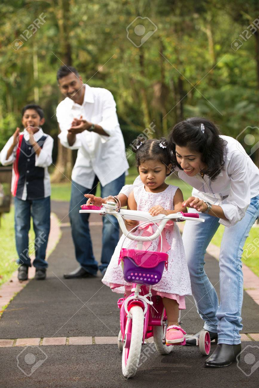 indian family guiding little daughter to cycle Stock Photo - 25114860