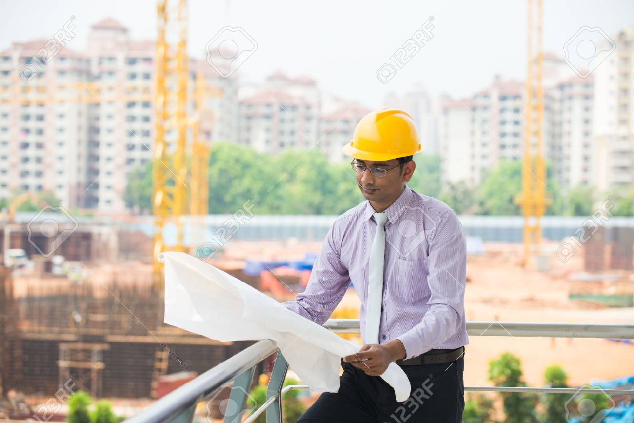 285320b3c5c indian male architect reading plans with construction background Stock  Photo - 26766105