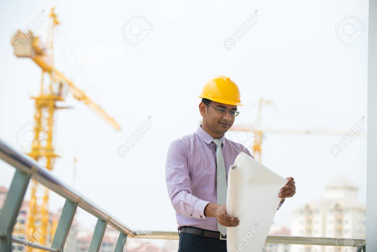 c5dc943b548 indian male architect reading plans with construction background Stock  Photo - 26766108