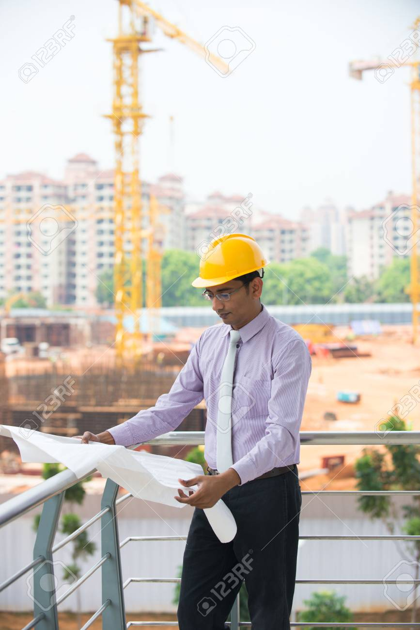 d95d74868ce indian male engineer reading plans with construction background Stock Photo  - 29265971