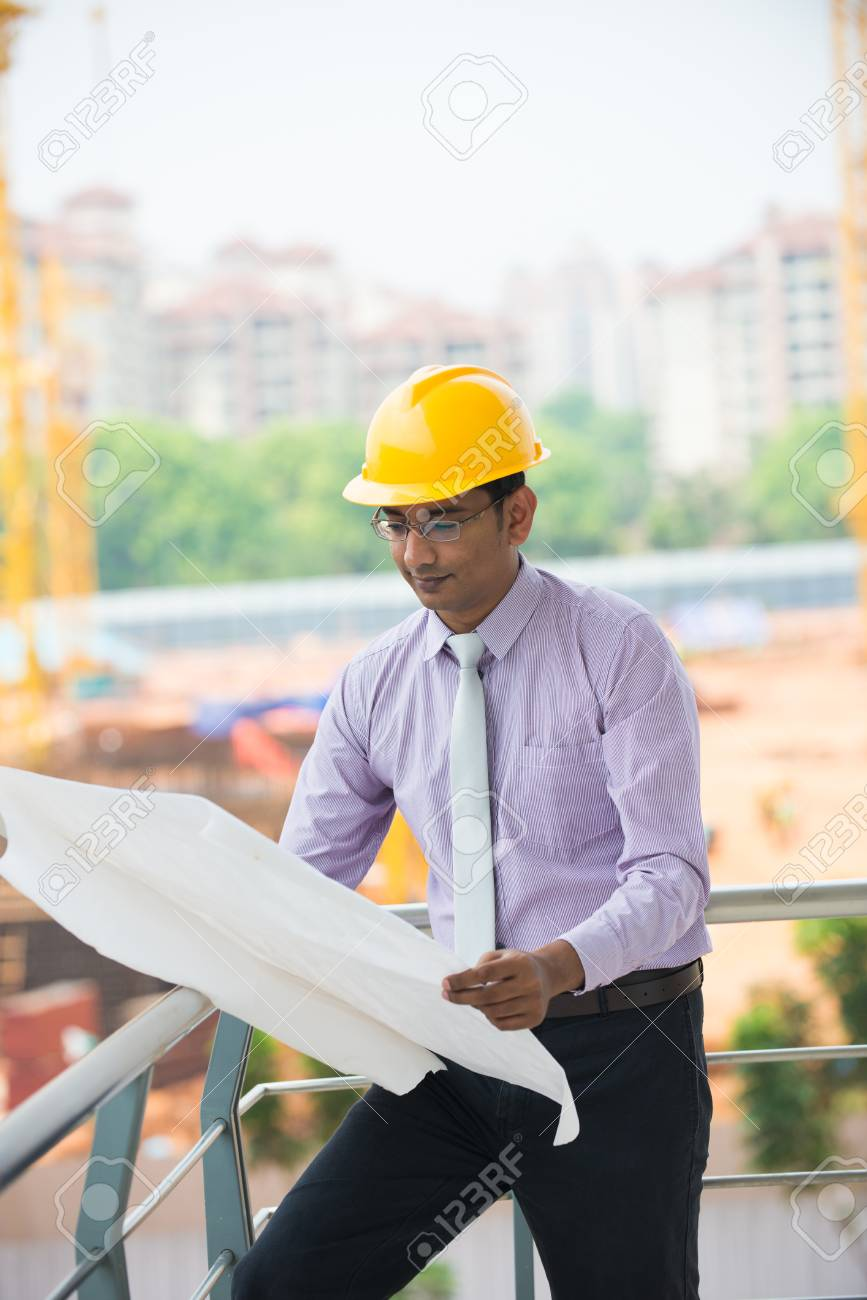 90264e8714c indian male engineer reading plans with construction background Stock Photo  - 29265972