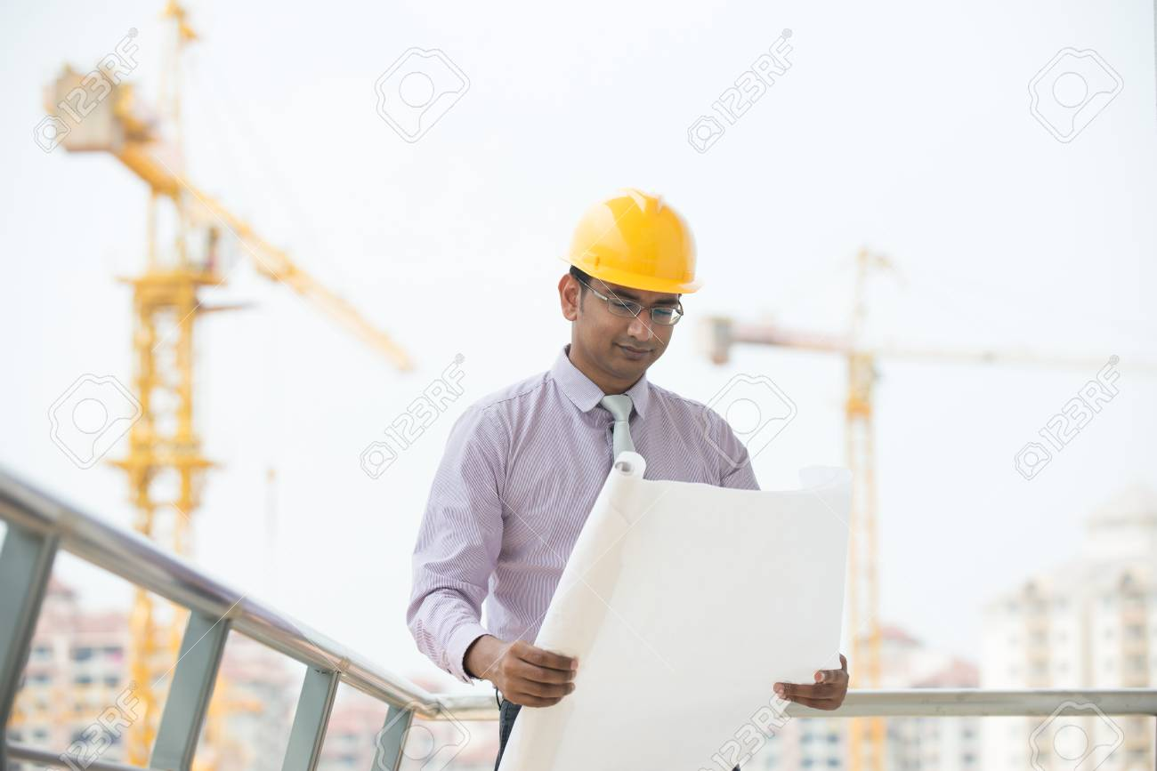 6bef68a5ddb indian male engineer reading plans with construction background Stock Photo  - 29265977