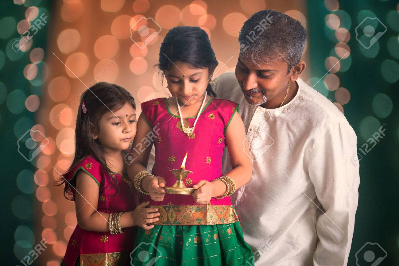 indian family fagther and daughter celebrating diwali ,fesitval of lights inside a temple Stock Photo - 29398993