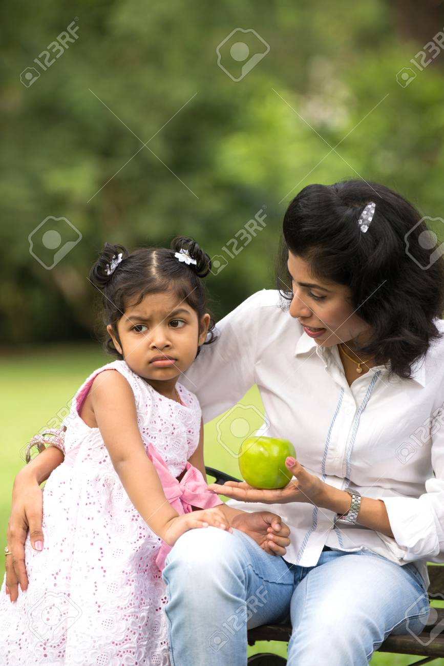 Indian mother and child eating healthy outdoor