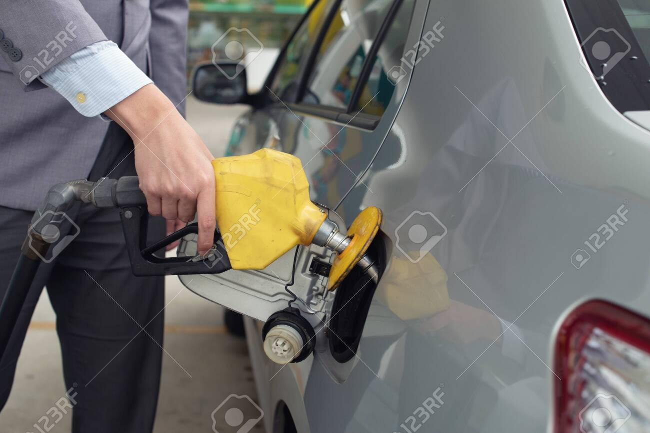 Pumping gas at gas pump. Closeup of man pumping gasoline fuel in car at gas station.M - 135095408