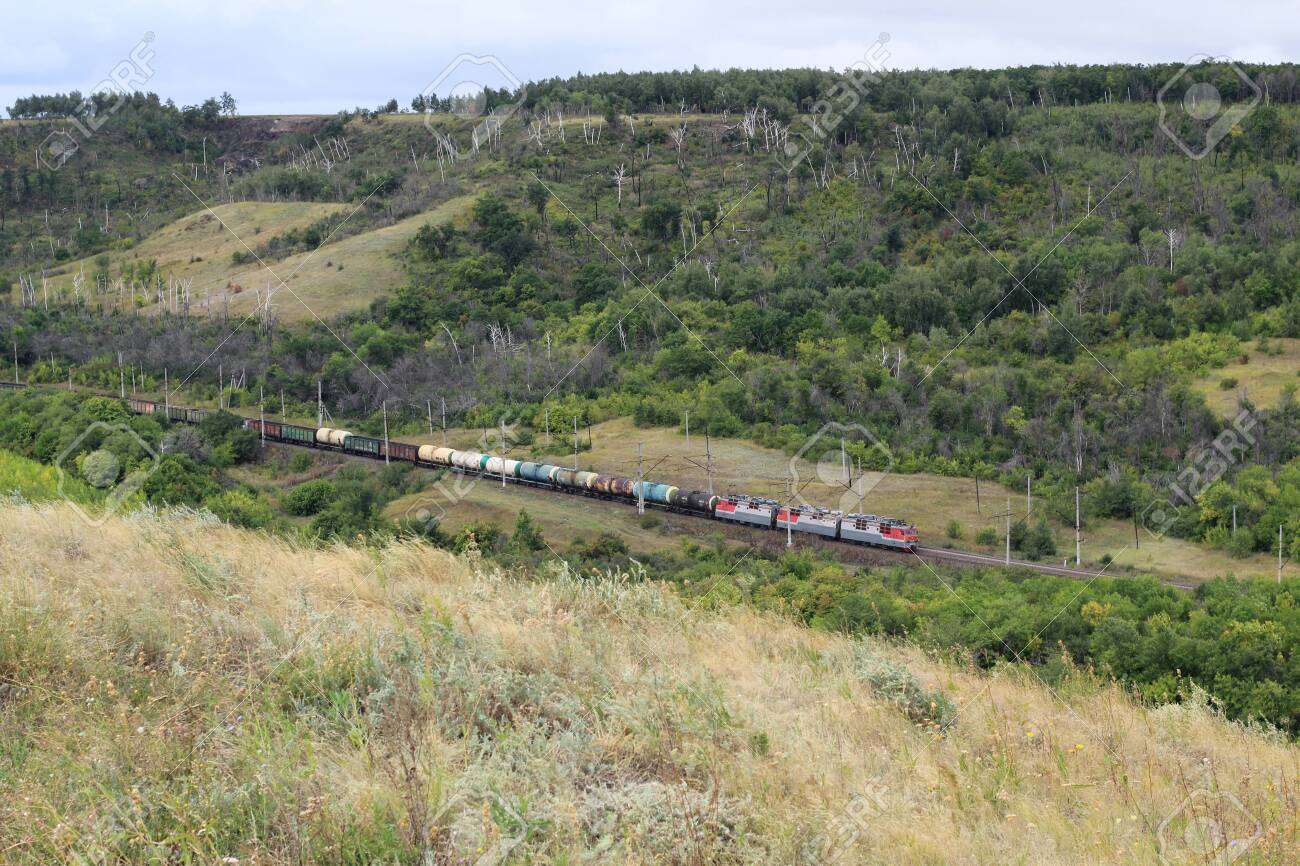 A long train loaded with double-stack cargo containers winds