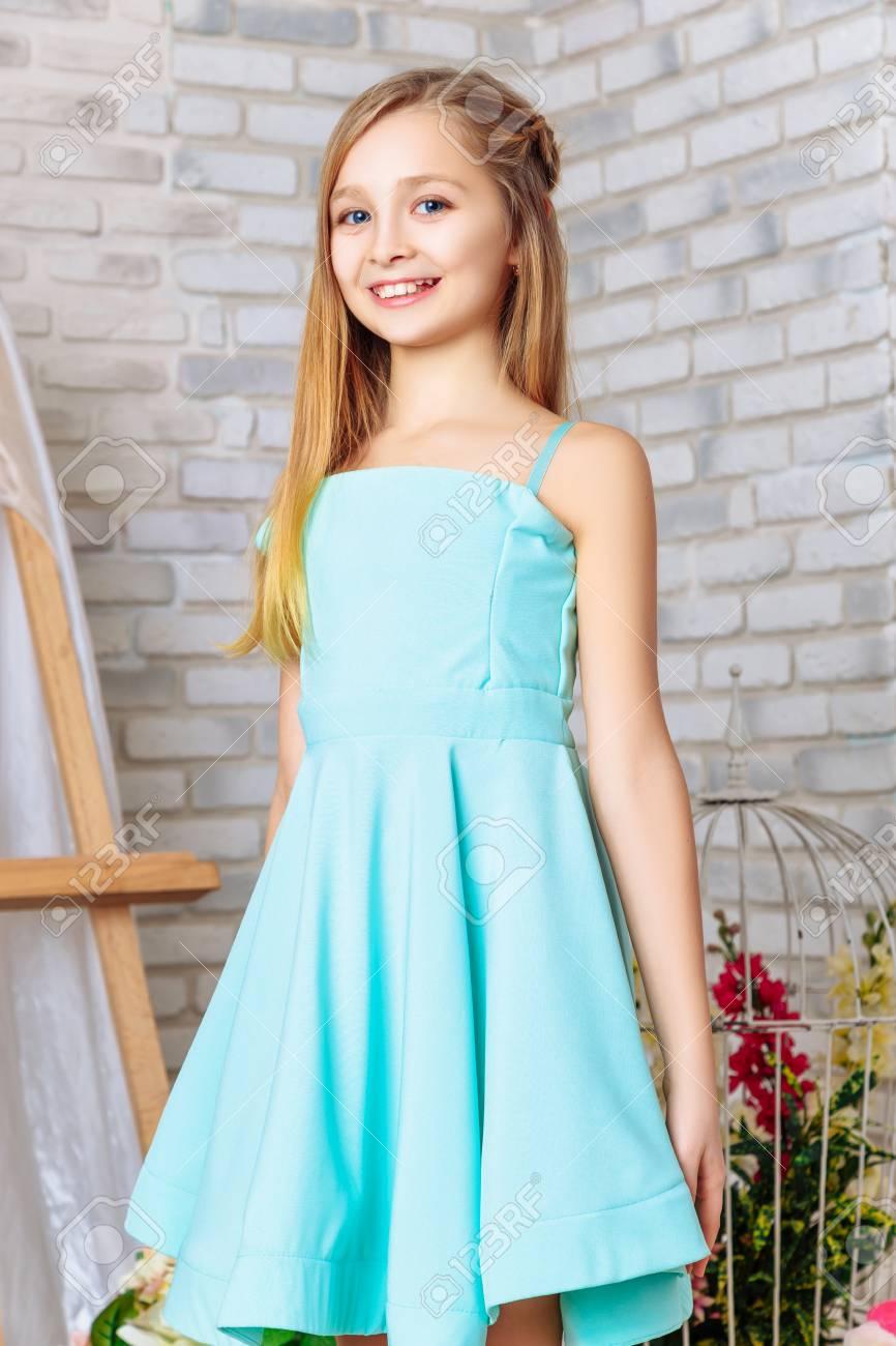 Hermosa Niña Con Maquillaje Perfecto Y Peinado En Estudio Interior Vestido Con Un Vestido Azul