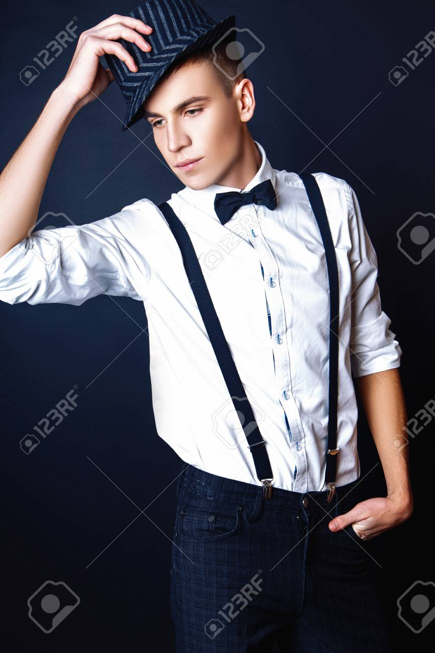 febd1eebd24 Attractive trendy young man dressed in a white shirt with suspenders and a  bow tie