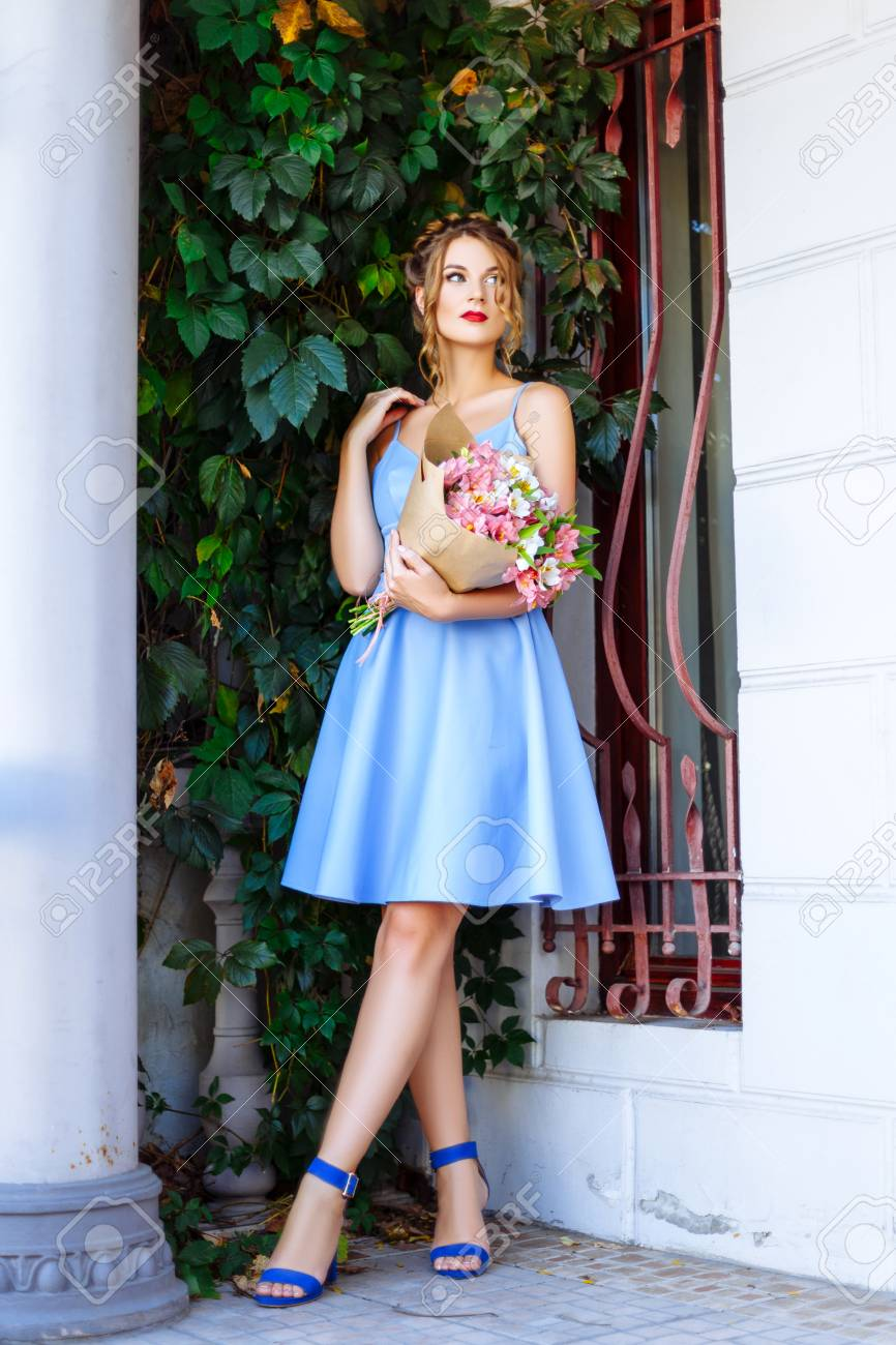 81742f40fb3 Cheerful girl in a blue dress with red lips and a stylish hairdo enjoying a  stroll