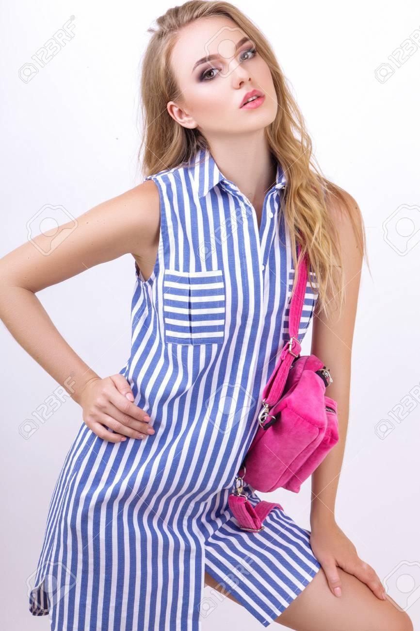 Banque d images - Belle jeune femme blonde qui pose en studio sur fond  blanc. La fille est vêtue d une robe rayée d été et tient un sac à dos rose faad9fb55af3