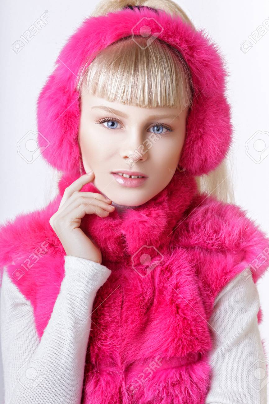 2356d8e898 beautiful blonde teen girl dressed in pink fur vest and earmuffs posing in  studio over white