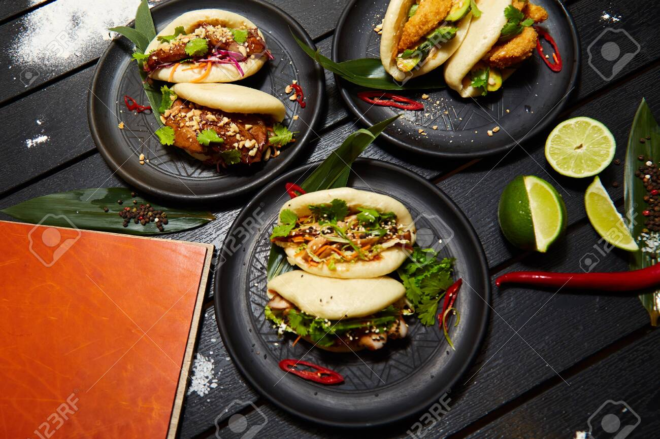 A Set Of Three Asian Dishes On Black Plates On A Wooden Table Stock Photo Picture And Royalty Free Image Image 128484759