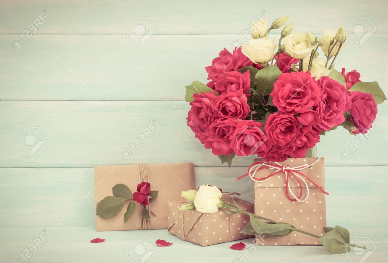 https://previews.123rf.com/images/yuliiajd/yuliiajd1707/yuliiajd170700158/82688981-rosen-bouquet-und-geschenke-auf-h%C3%B6lzernen-hintergrund-in-shabby-chic-stil-feierliches-interieur-leerer-.jpg