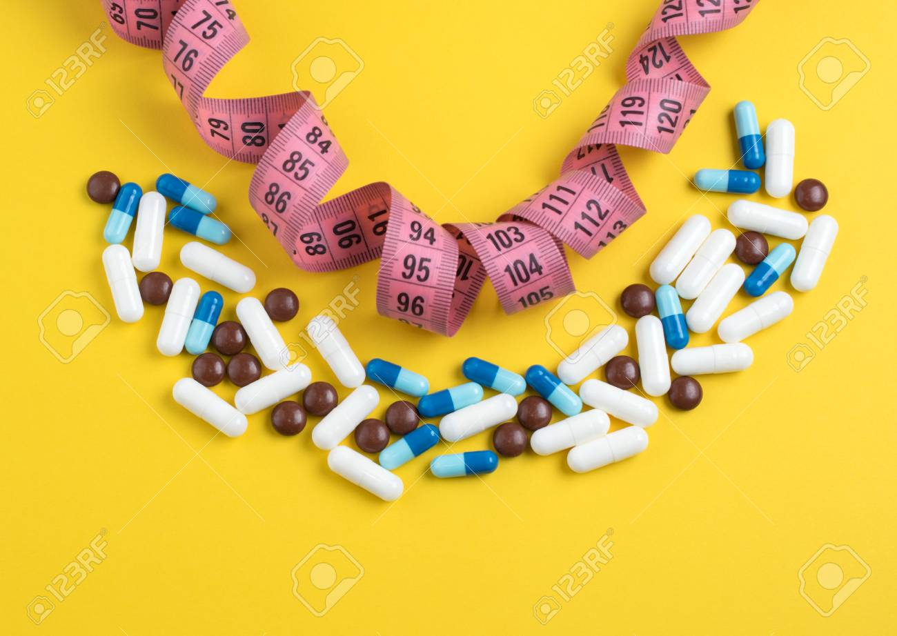 Diet pills for losing weight. Pharmaceutical colorful capsules and  centimeter on yellow