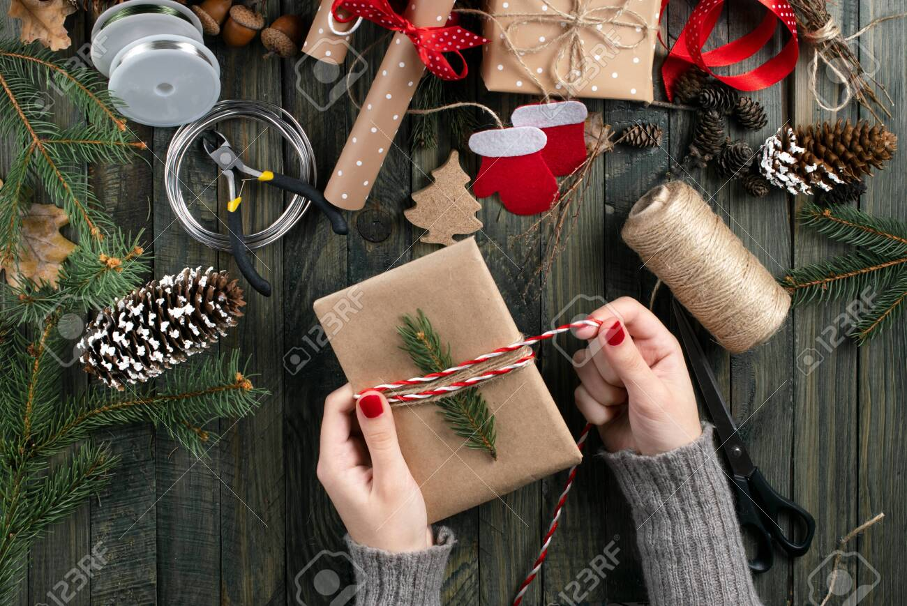 Christmas workshop theme. Top view of woman hands wrapping New Year present and tie bow. Packed gifts and scrolls, spruce branches and tools on shabby wooden table. - 121817968