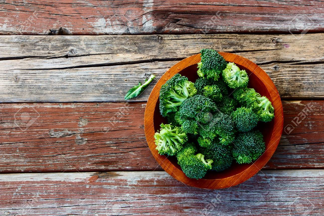 Fresh green broccoli in wood bowl over rustic wooden background - healthy or vegetarian food concept Top view. - 46934233