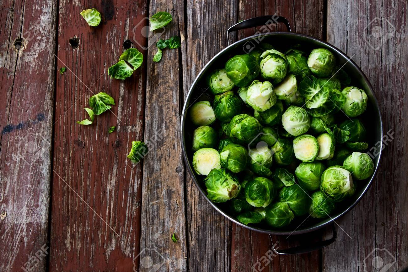 Fresh brussel sprouts over rustic wooden texture. Top view. - 47357345