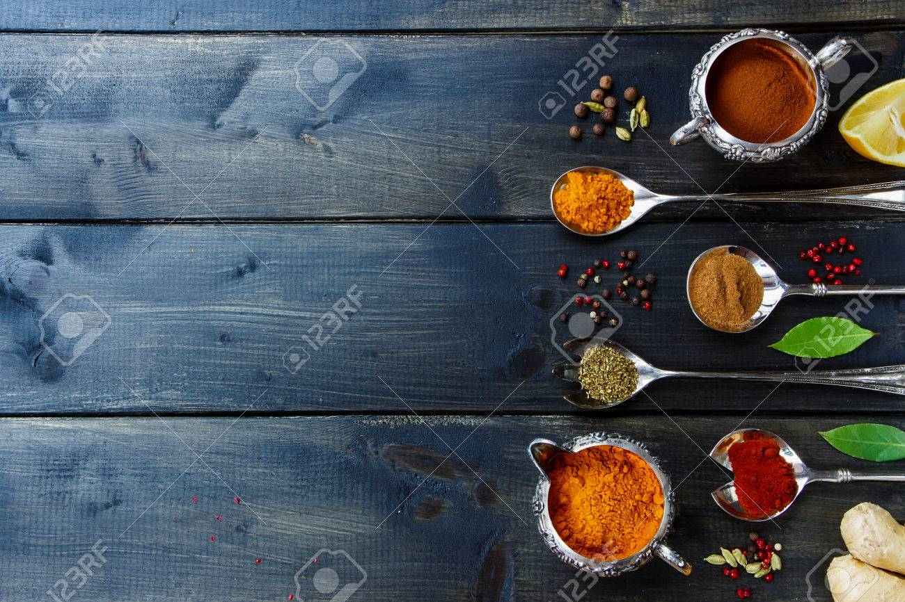 Various powder spices in old metal cups and spoons over dark wooden table. Background with space for text. Food or cooking concept. Top view. - 47984370