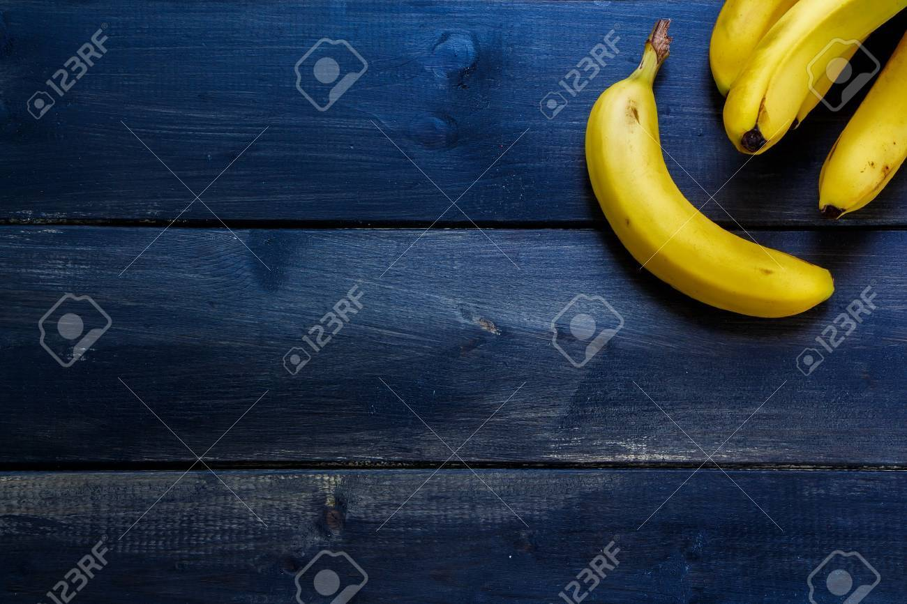 Fresh bananas on rustic wooden board. Healthy eating background with space for text. - 47984498