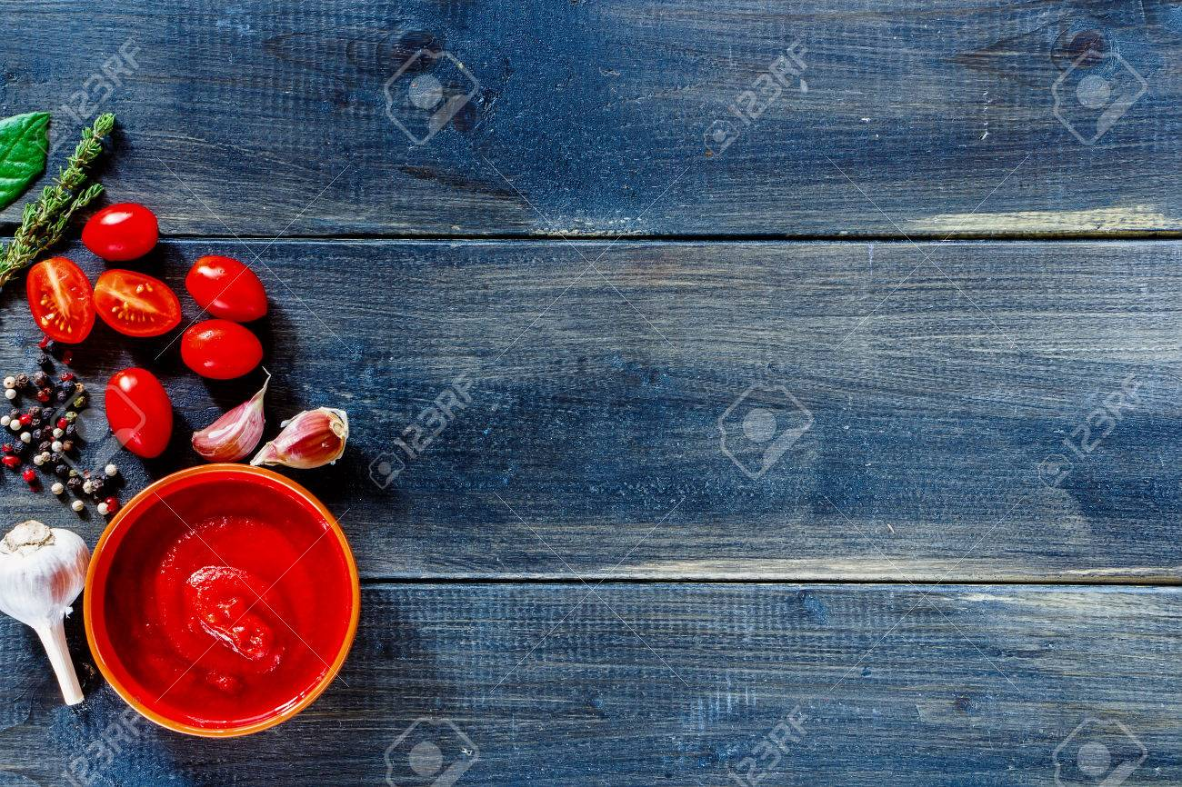 Background with tomato sauce ingredients (cherry tomatoes, fresh herbs, garlic, pepper) over dark wooden board. - 48653249