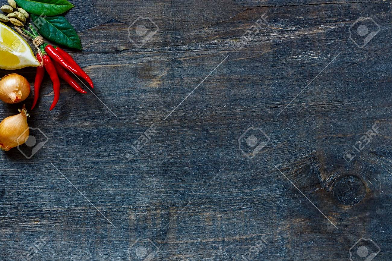 Top view on red hot chili peppers, onions, lemon and spices over dark wooden background with copyspace. - 48652863