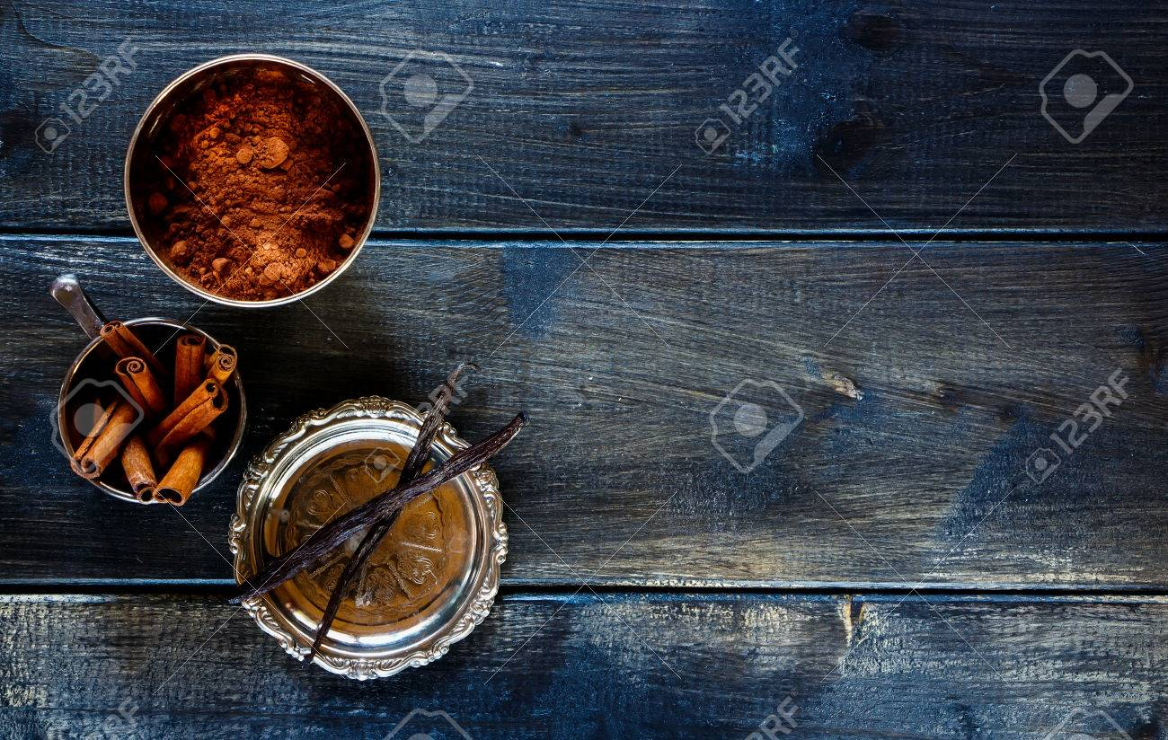 Food background with cocoa powder, vanilla and cinnamon sticks over dark wood. Christmas and holidays concept. Copy space. Top view. - 49744474