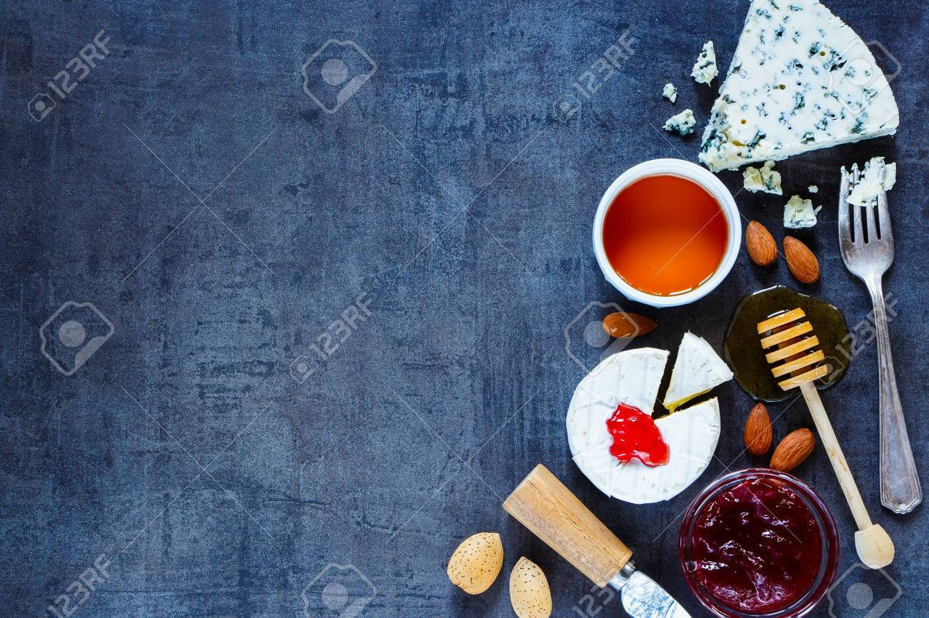 Variety of cheese with honey, fruity jam and nuts over dark vintage texture. Top view. Background layout with free text space. Healthy food. Cheese appetizer selection. - 54733495