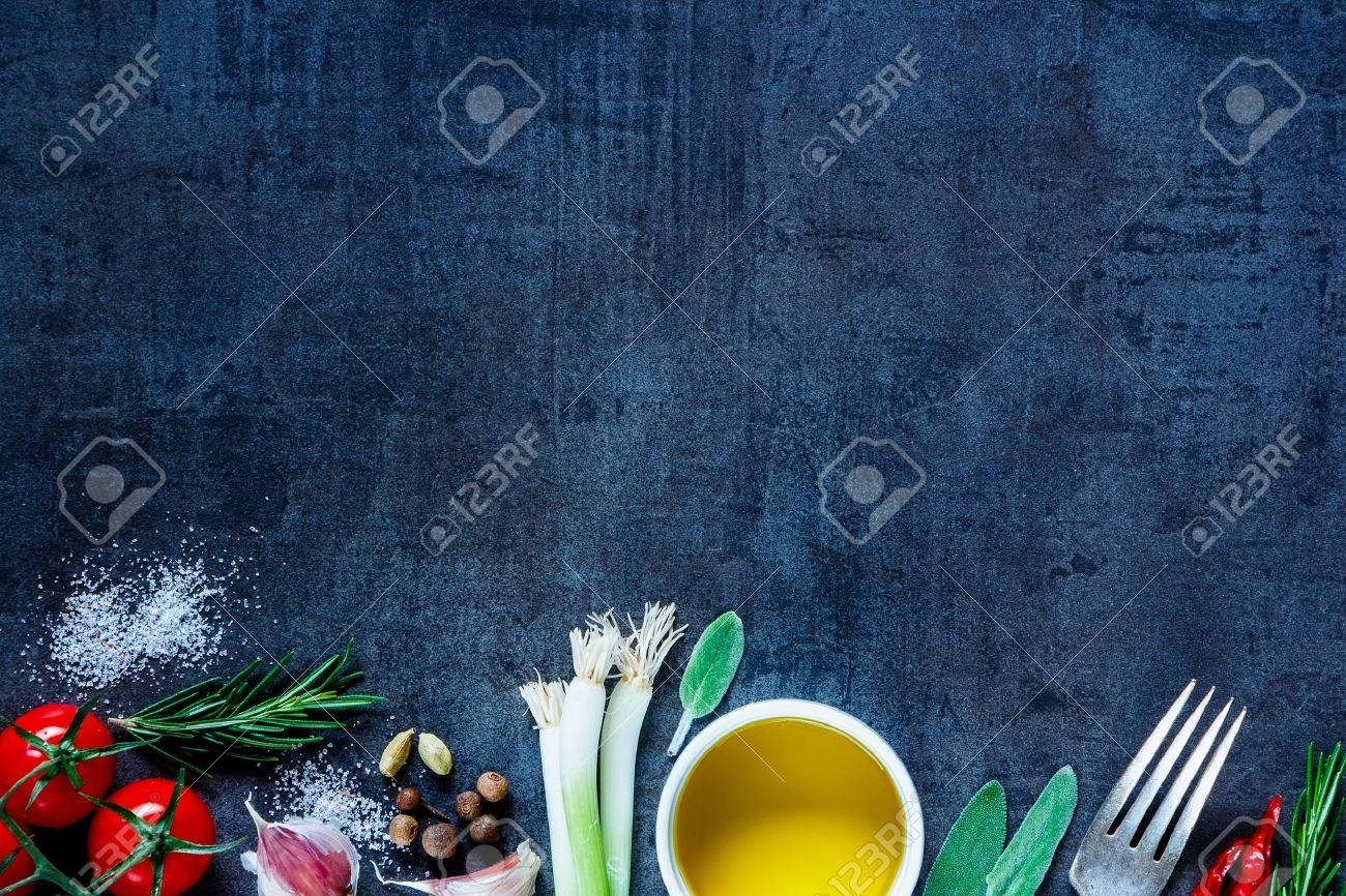 Top view of olive oil and fresh cooking ingredients (young green onions, peppercorns, tomatoes, garlic, rosemary) on dark vintage background. Top view. - 54733421