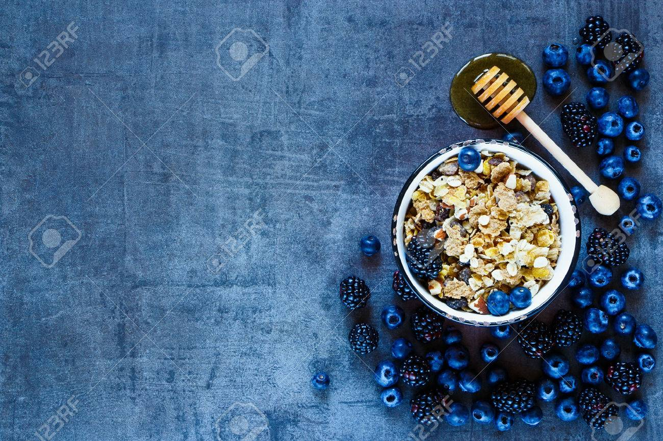 Granola in vintage mug, dark berries and honey for delicious breakfast on grunge background with space for text on left, top view. - 54733180