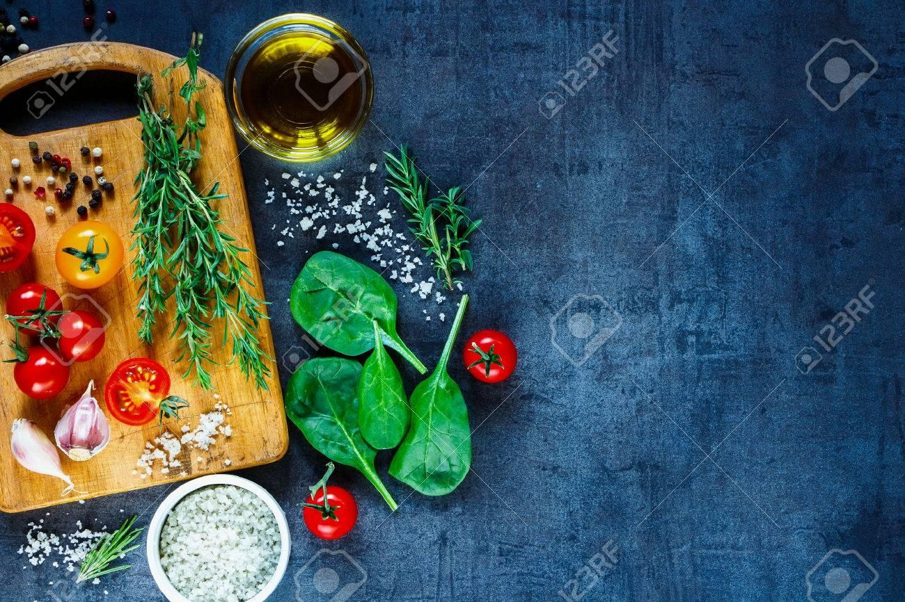 Organic vegetarian ingredients, olive oil and seasoning on rustic wooden cutting board over dark vintage background with space for text, top view. - 54733183
