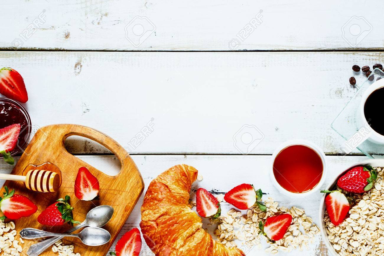 Delicious rural breakfast with oats, fresh strawberries, cup of coffee, fruity jam, honey and croissant on rustic white wooden background with space for text. Top view. - 54733150