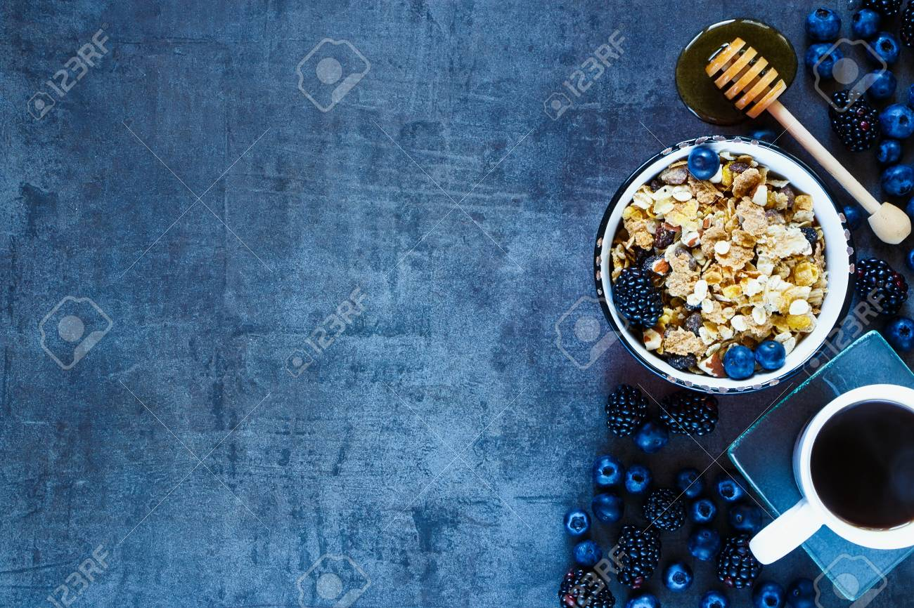 Tasty granola in vintage mug, dark berries, coffee and honey for delicious breakfast on grunge background with space for text on left, top view. - 54733167