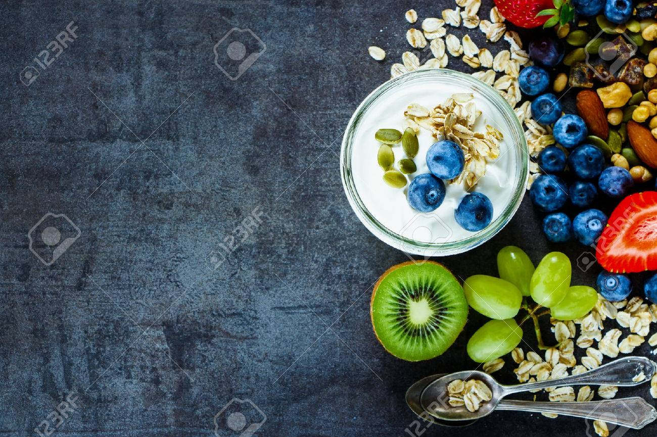 Close up of tasty ingredients (oat flakes, green grapes, kiwi, berries with yogurt and seeds) for breakfast or smoothie on dark vintage background - 54732720