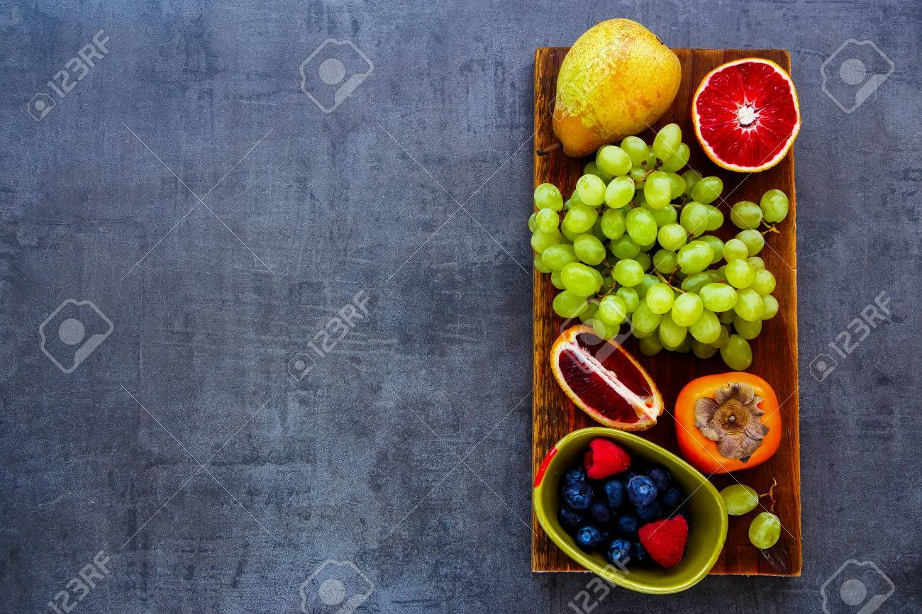 Various organic fruit selection on rustic wooden chopping board over slate background, top view. Agriculture, Gardening, Harvest Concept. Detox, dieting, clean eating, vegan, fitness, healthy lifestyle concept - 72311371
