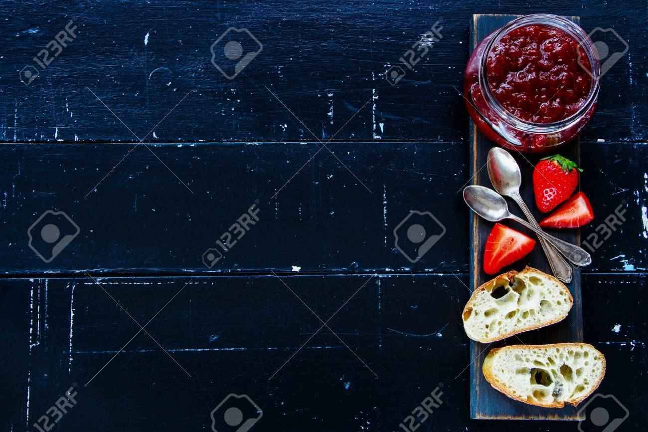 Traditional breakfast - Freshly baked and sliced French baguette with strawberry jam on wooden board over black vintage background, top view, copy space. - 73567086