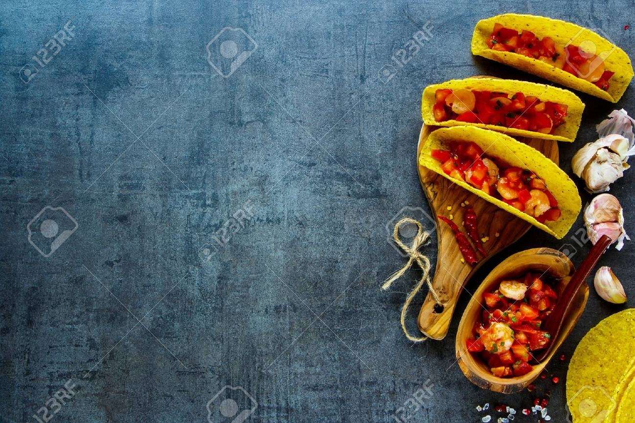 Fresh shrimp tacos with homemade salsa on wooden board over dark slate background. Top view, copy space. Mexican cuisine concept - 82449951