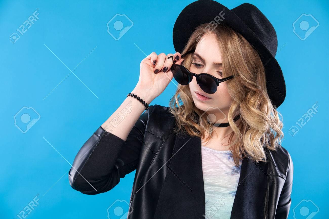 tout à fait stylé dernière collection enfant Femme hipster de mode posant à l'extérieur sur un backgrund bleu. Chapeau  noir, veste en cuir, cheveux bouclés blond, lèvres rouges brillantes, ...