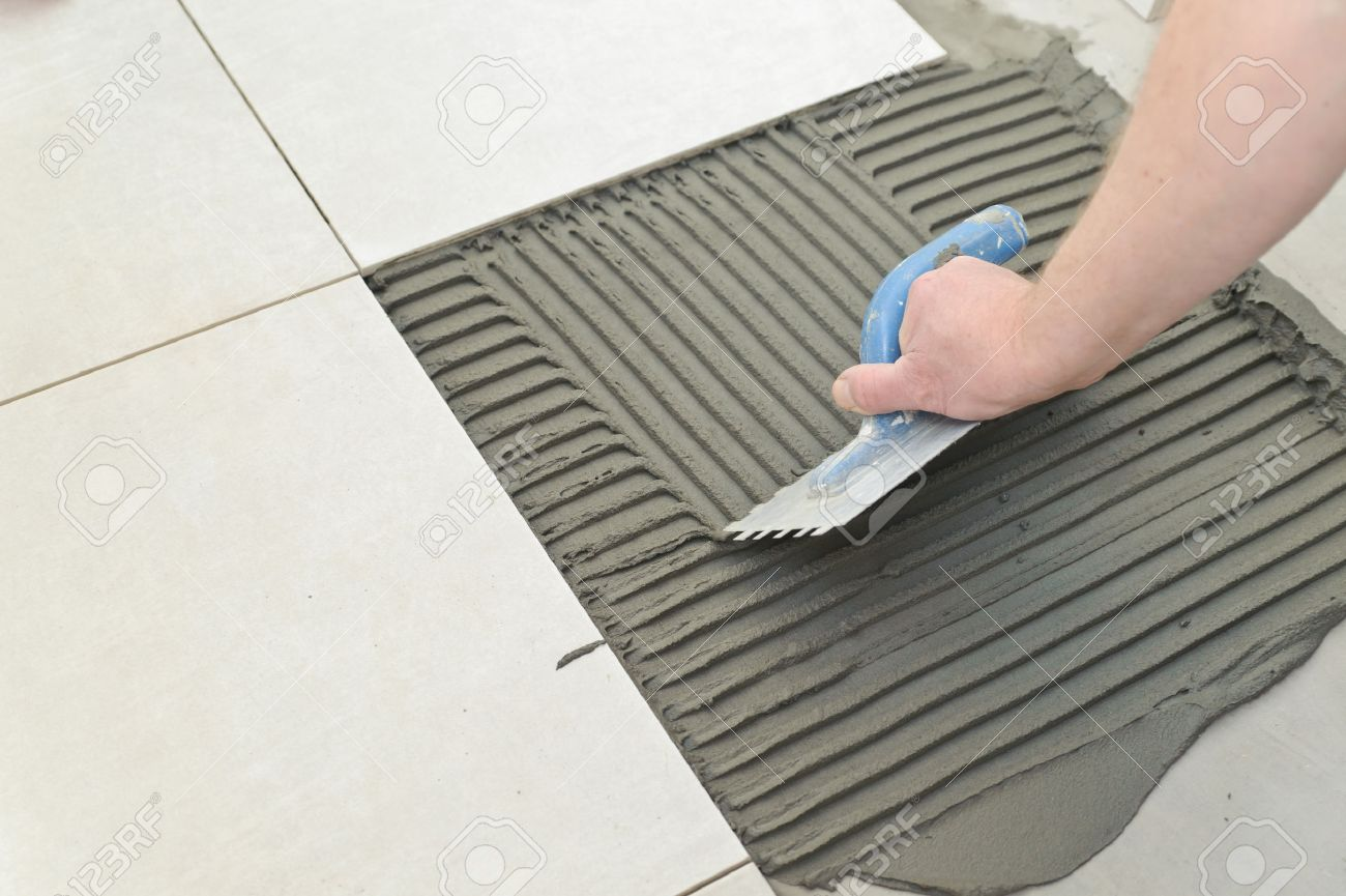 Laying Ceramic Tiles. Troweling Mortar Onto A Concrete Floor.. Stock ...