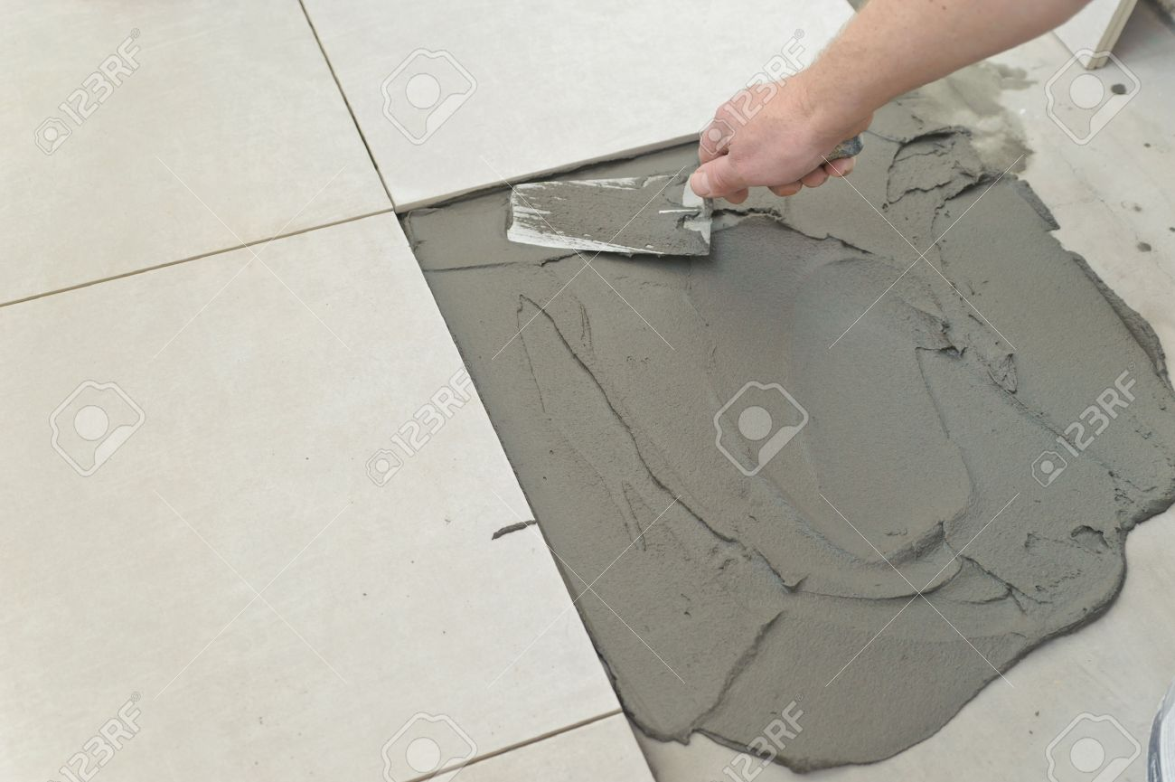 Laying ceramic tiles troweling mortar onto a concrete floor stock laying ceramic tiles troweling mortar onto a concrete floor in preparation for laying white floor dailygadgetfo Choice Image