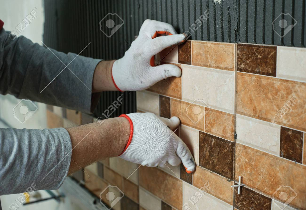 Laying Ceramic Tiles. Tiler Placing Ceramic Wall Tile In Position ...