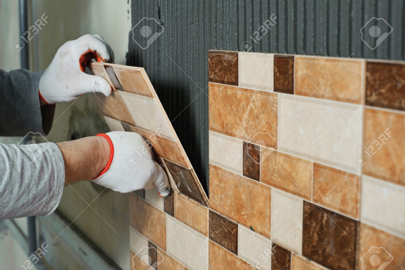 Laying ceramic tiles tiler placing ceramic wall tile in position laying ceramic tiles tiler placing ceramic wall tile in position over adhesive stock photo dailygadgetfo Image collections
