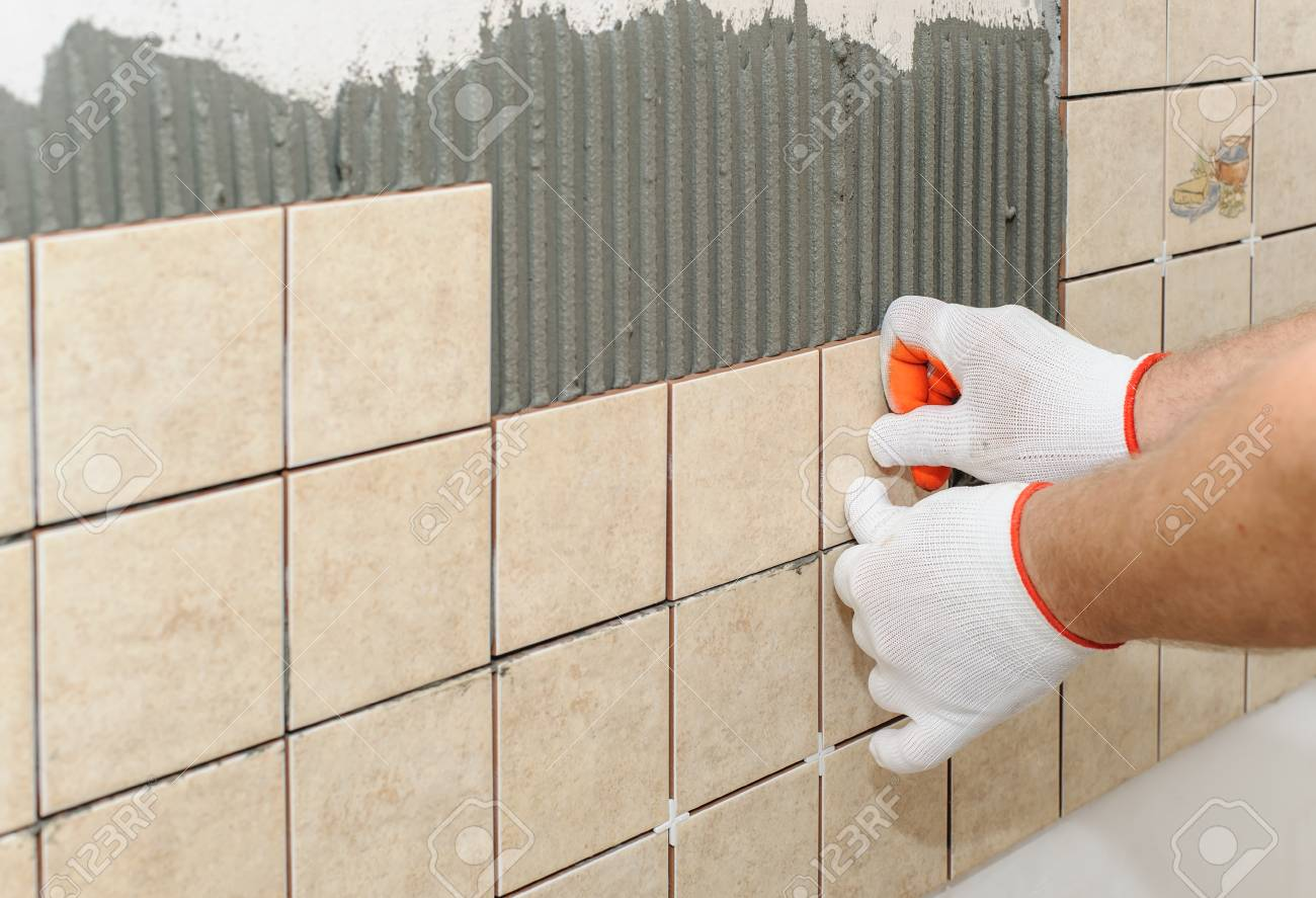 Worker Sets Tiles On The Wall In The Kitchen. His Hands Are.. Stock ...