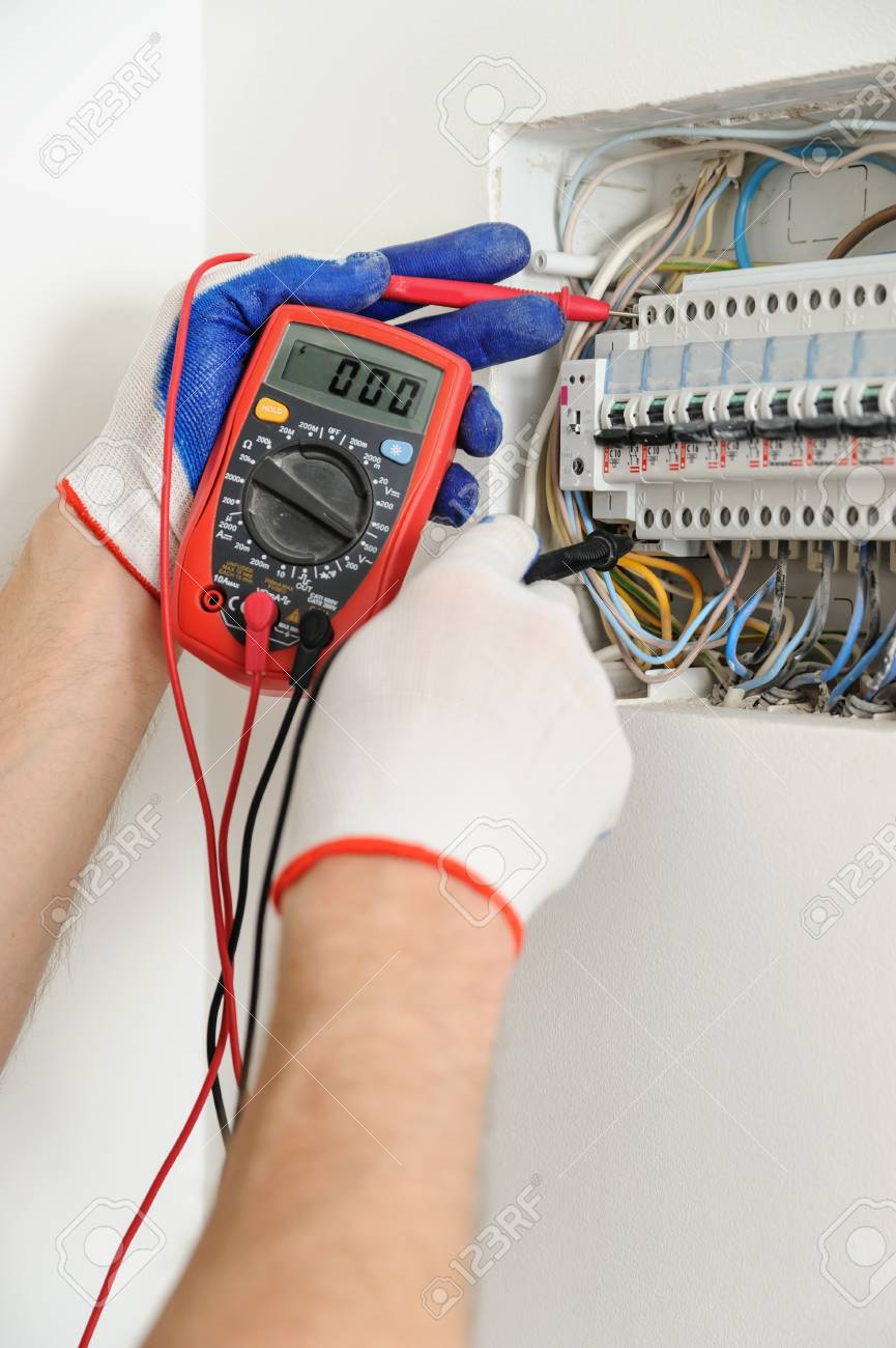 electrician check voltage in electrical fuse box with a multimeter ...  123rf.com